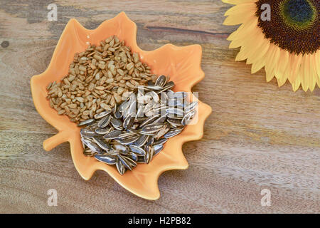 Sunflower seeds in leaf-shape harvest bowl, decorated with yellow sunflower, on wooden background - Stock Photo
