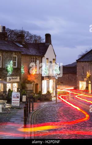 Both Christmas and trail lights add colour on a dark winter night - Grassington Village, Yorkshire Dales National - Stock Photo