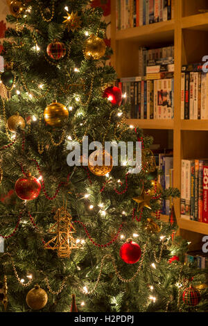 Detail of artificial Christmas tree, decorated with reds and golds and pretty fairy lights twinkling - private house, - Stock Photo