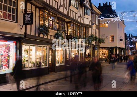 On a dark winter evening, Christmas shoppers pass by in a blur of movement - a festive, illuminated Stonegate, York, - Stock Photo