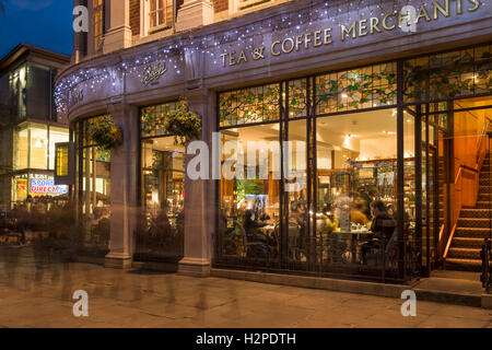 Exterior evening view of Betty's Café Tea Room at Christmas, diners seated by the window, bathed in warm light  - Stock Photo
