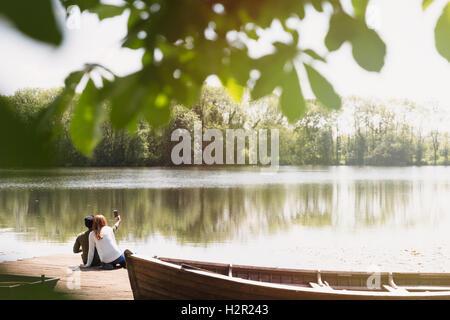 Couple with camera phone taking selfie on sunny lakeside dock next to canoe - Stock Photo