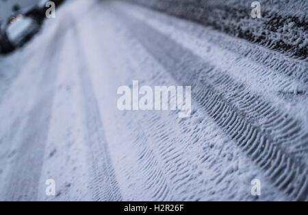 Tracks of car tires on a snow covered, glazed, icy street during a cold winter night - Stock Photo