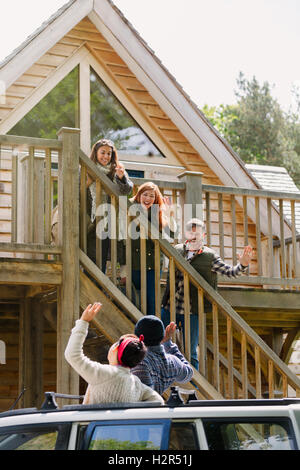 Friends on stairs waving to friends in car outside sunny cabin - Stock Photo