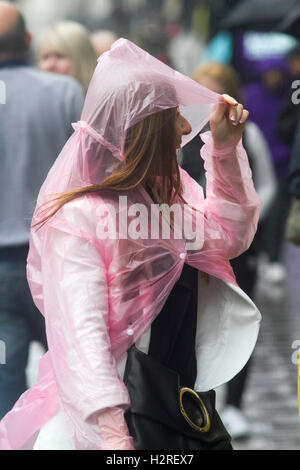 Wimbledon London, UK. 1st October 2016. A Shoppers covers her head  from the rain with pink plastic poncho in Tottenham - Stock Photo