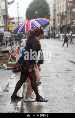 Wimbledon London, UK. 1st October 2016. Shoppers sheltering from the rain with ponchos and umbrellas in Tottenham - Stock Photo