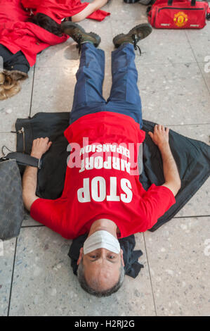 Heathrow, London, UK. 1st October 2016. A woman lies on the floor  wearing a t-shirt 'STOP airport expansion' at - Stock Photo