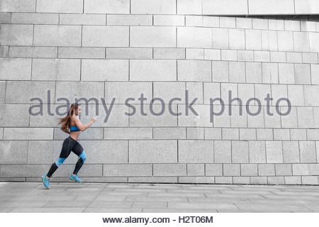 Runner athlete running on gray background. Woman fitness jogging workout. Wellness concept. - Stock Photo