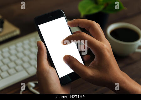 closeup hand use phone showing white screen on work desk, blank phone screen with clipping path easy for adjust - Stock Photo