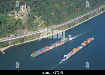 CONTAINER CARRIERS ON THE HEAVILY TRAVELED RHINE (aerial view). Rheinstein Castle, Rhineland-Palatinate, Germany. - Stock Photo