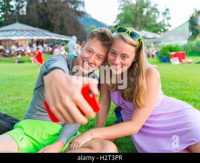 Young man and young woman smiling, taking photo with mobile phone, selfie, Bavaria, Germany - Stock Photo
