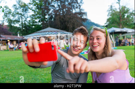 Young man and young woman smiling, looking at mobile phone, Bavaria, Germany - Stock Photo