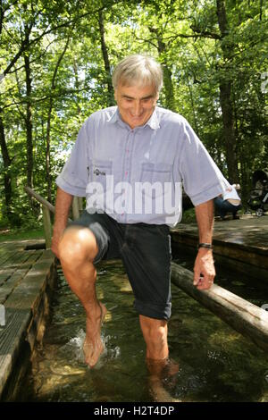 Senior citizen taking a hydrotherapy treatment in a Kneipp bath - Stock Photo