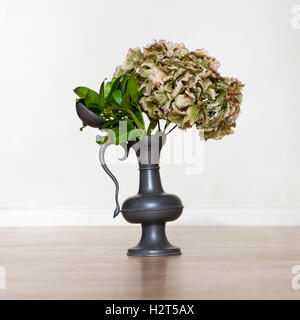 Flowers in an old tin vase - Stock Photo