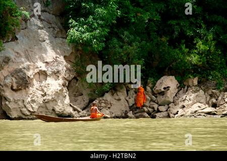 2 young monks taking wooden canoe to cross Nam River in Laos - Stock Photo