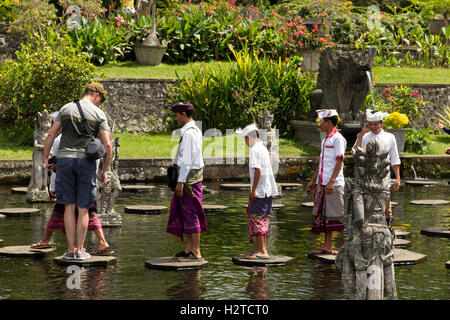 Indonesia, Bali, Tirta Gangga, Ababi, Palace, local tourists wearing traditional costume in water garden pool