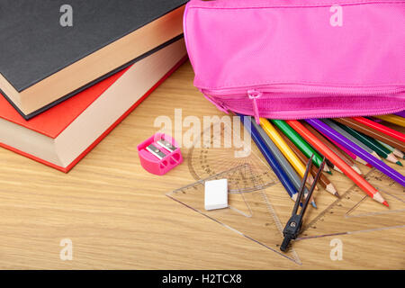 Coloring pencils spilling out of a pink pencil case on a desk with a pink sharpener and books - Stock Photo