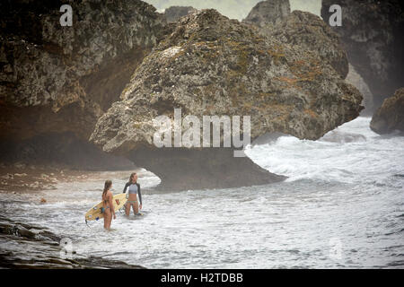 Barbados atlantic coast Bathsheba rocks   pretty Young girls ladies teenagers surfing surfers copyspace large boulder - Stock Photo