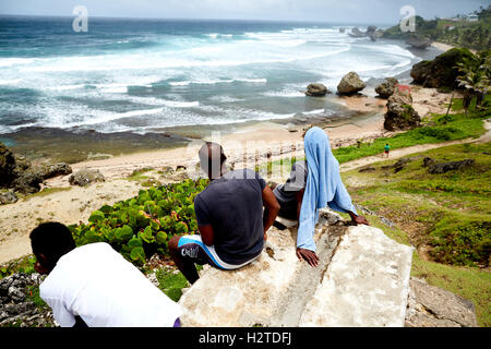 Barbados atlantic coast view ocean  local men boys sat looking out to sea relaxed resting sat on stone beech Elevated - Stock Photo