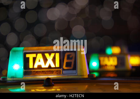 Row of taxi signs from parked taxis in a city street at night - Stock Photo