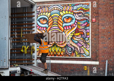 Pedestrian walking past street art, graffiti wall painting, decoration, at the Sun, Spray and Art Festival Art in - Stock Photo