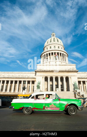 HAVANA - JUNE 17, 2011: Classic American Cuban taxi car passes in front of the Capitolio building in Central Havana. - Stock Photo