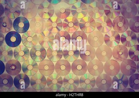 Background on the wall with old damaged discs cd in vintage style. - Stock Photo