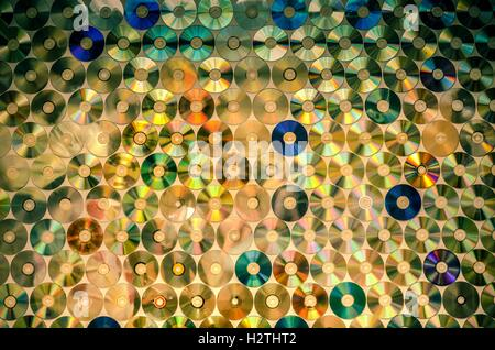 Background on the wall with old damaged discs cd. - Stock Photo