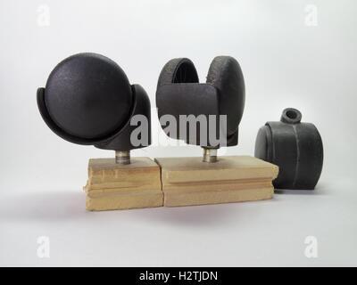Three black castors for furniture - Stock Photo