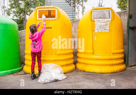 Containers of plastic for waste separation. Girl places plastic into a collector to recycle,recycling center - Stock Photo