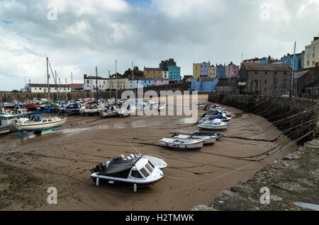Landscape photo of small fishing boats and dinghies awaiting next incoming tide in Tenby Harbour, Pembrokeshire, - Stock Photo