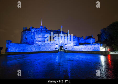 Edinburgh Castle at night bathed in Saltire Blue light - Stock Photo