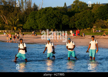 Hotel workers walking in Tamarin beach, Mauritius. Relection in the water. - Stock Photo