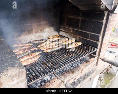 Sardines Roasting on an Azorian BBQ. A grill full of grilling sardines or mackerel cooks on a brick BBQ over a hot - Stock Photo