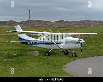 Cessna Stationair 6 light aircraft tethered to concrete blocks on grass at Colonsay airstrip, Isle of Colonsay, - Stock Photo