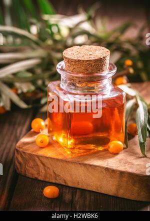 Small bottle of sea buckthorn oil - Stock Photo