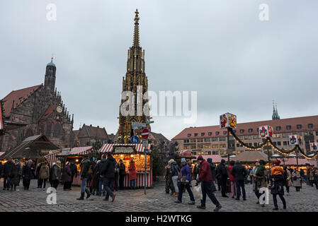 At dusk Christmas shoppers around the 14th century fountain in Hauptmarkt (Market Square) during the Nuremberg Christmas - Stock Photo
