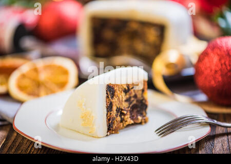 Slicing Christmas traditional festive fruit cake, Christmas ornaments and decorations - Stock Photo