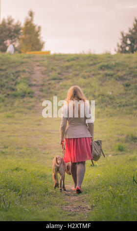 rear view young adult overweight woman walking dog summer - Stock Photo