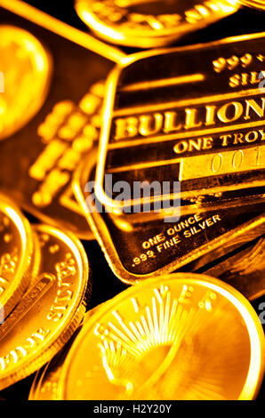 Several stacks of gold coins and bars representing wealth