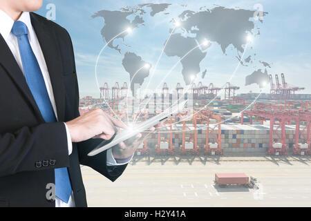 Import, Export, Logistics concept - Businessman press digital tablet to show global network partnership connection - Stock Photo