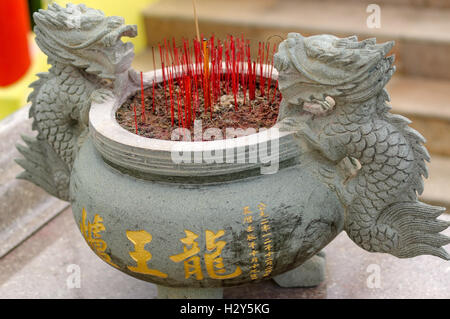 a burning Incense sticks in joss-stick pot in a chinese buddhism temple in Penang, Malaysia - Stock Photo