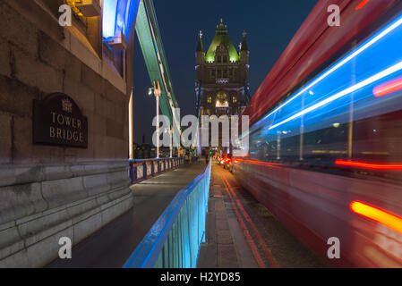 Blurred routemaster bus and gleam of traffic on the Tower Bridge over the river Thames at night, London, UK - Stock Photo