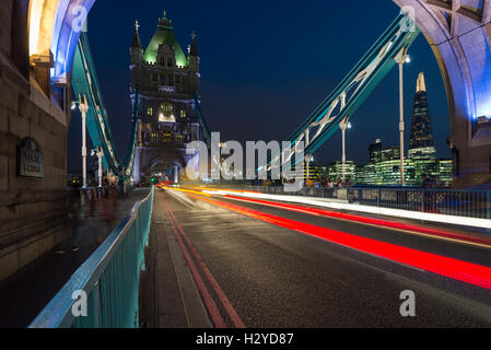 Skyline of Southwark with the Shard and gleam of traffic on the Tower Bridge over the river Thames at night, London, - Stock Photo
