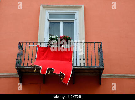 The medieval red flag on the balcony of an apartment house. - Stock Photo