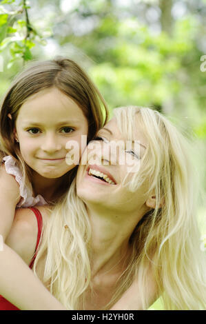 Young mother with her daughter in a garden - Stock Photo