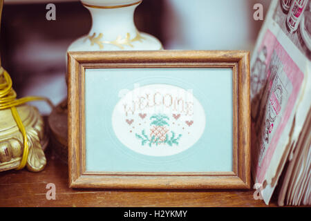 Cute vintage framed welcome crosstich - Stock Photo