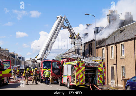 Scottish Fire and Rescue Service firefighters up a ladder fighting a burning building in Elie and Earlsferry, Fife, - Stock Photo