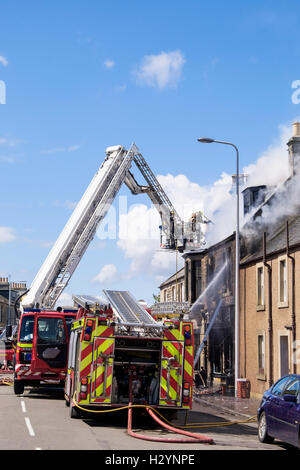 Scottish Fire and Rescue Service firefighters up a ladder tackling a burning building in Elie and Earlsferry, Fife, - Stock Photo