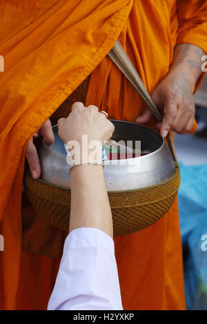 Hand put food offerings in a Buddhist monk's alms bowl - Stock Photo
